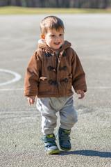 A little boy is walking on a sports field