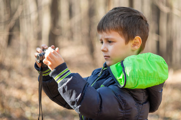 Boy photographing in the forest. Boy photographing nature with a compact camera.