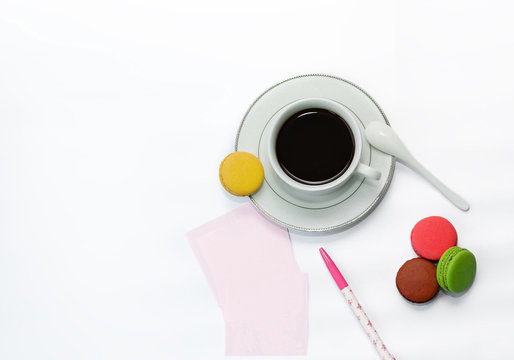 cup with coffee and macrons, pen and note paper.