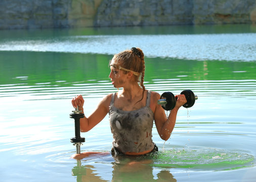 A young teenage girl is weightlifting in a green lake. She wears torn and dirty clothes and uses steel weights to train her body.