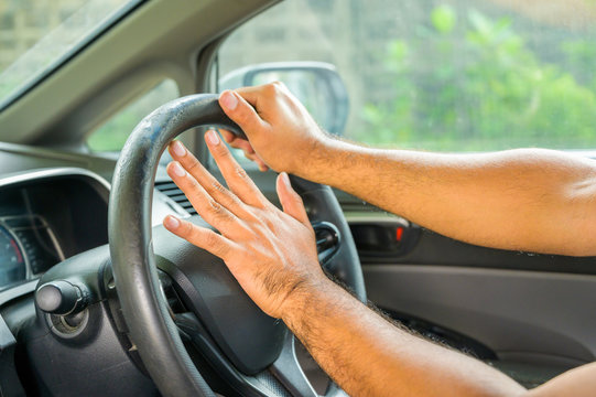 Closeup hands pushing on steering wheel honking horn in his car. Safety concept