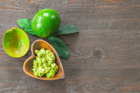 avocado and avocado puree in a wooden bowl top view. background with avocado and avocado puree on the table close-up.