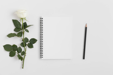 Top view of a notebook mockup with a rose on a white table.