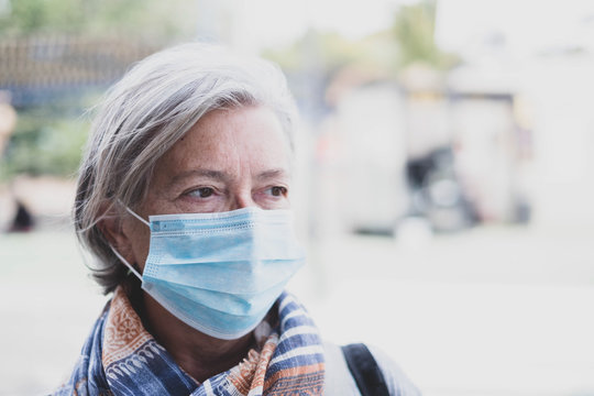 close up of face of mature woman looking away wearing medical mask prevention coronavirus or covi-19 or another type of virus - senior seriously worried and prevention be infected