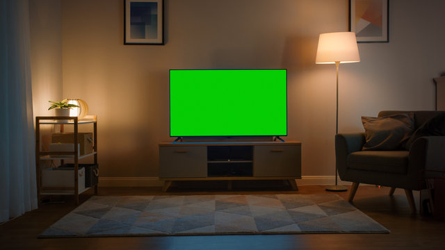 Shot Of A Tv With Horizontal Green Screen Mock Up Cozy Evening Living Room With A Chair And Lamps Turned On At Home Stock Photo Adobe Stock