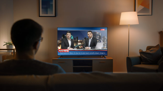 Young Man in Glasses is Sitting on a Sofa and Watching TV with Live News. It's Evening and Room at Home Has Working Lamps.
