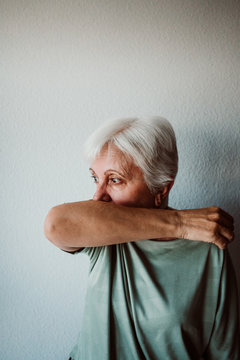 Senior woman coughing into elbow