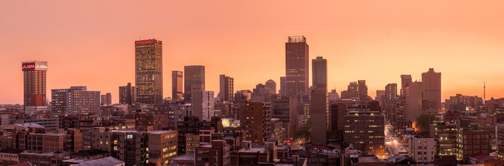 Foto auf Leinwand Dunkelbraun A beautiful and dramatic panoramic photograph of the Johannesburg city skyline, taken on a golden evening after sunset.