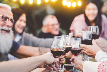 Happy family dining and toasting red wine glasses in barbecue dinner party - People having fun eating together - Youth and elderly parents and food weekend activities concept