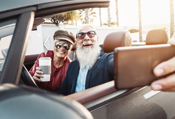 Happy senior couple taking selfie on new modern convertible car - Mature people having fun together making self photos during road trip vacation - Elderly lifestyle and travel transportation concept