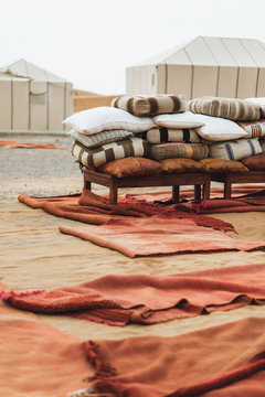 Detail of contemporary luxury glamping camp in Morocco Sahara desert. Heap of many different pillows and red rug carpets.
