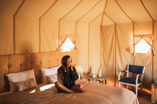 Sensual glamour portrait of oriental woman in interior of modern luxury glamping tent camp in Morocco. Relaxing on bed. Eco design concept, natural and wooden elements in style.