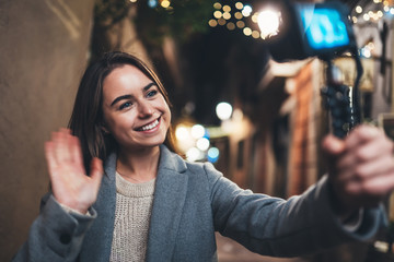 Fotomurales - Female blogger showing hi recording video for vlog social media with digital camera. Smiling woman vlogger taking photo selfie on background illuminations light night city