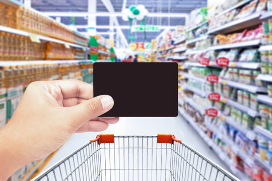 Hand holding credit card with supermarket background