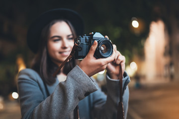 Fotomurales - Photographer tourist girl with retro camera take photo on background bokeh light in evening europe city, Blogger photoshoot photo hobby