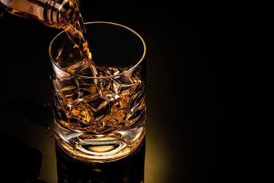 glass of whiskey on black background
