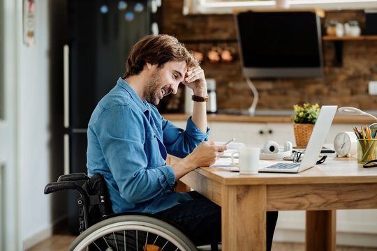 Happy disabled entrepreneur reading text message on cell phone while working at home.