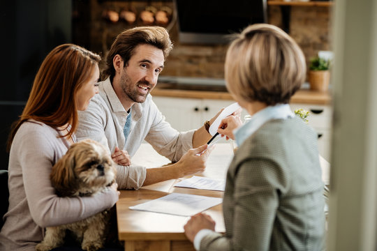 Happy couple communicating with insurance agent while having a meeting at home.