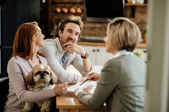 Young couple with a dog having a meeting with financial advisor at home.