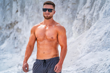 Printed kitchen splashbacks Artist KB Fitness athlete in sunglasses posingoutdoor. Preparing for training in a quarry. Photoshoot in white mountains. Strong attractive bodybuilder. Lifestyle. White landscape.