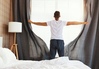 Anonymous man pulling curtains in morning. Fotomurales