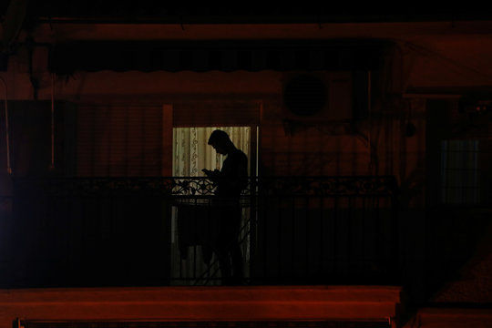 A man checks his mobile phone on a balcony as he remains confined inside his home due to the coronavirus outbreak, in downtown Ronda
