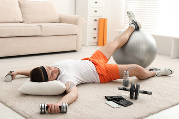 Lazy young man with sport equipment sleeping on floor at home