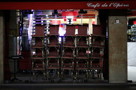 Outside seats are pilled up in a closed bar, as France's Prime Minister announced to close most all non-indispensable locations from midnight on Saturday, in Paris