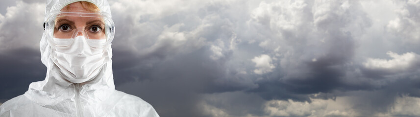 Female Medical Worker Wearing Protective Face Mask and Gear Against Cloudy Stormy Sky.