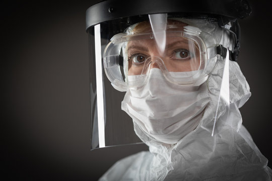 Female Medical Worker Wearing Protective Face Mask and Gear Against Dark Background