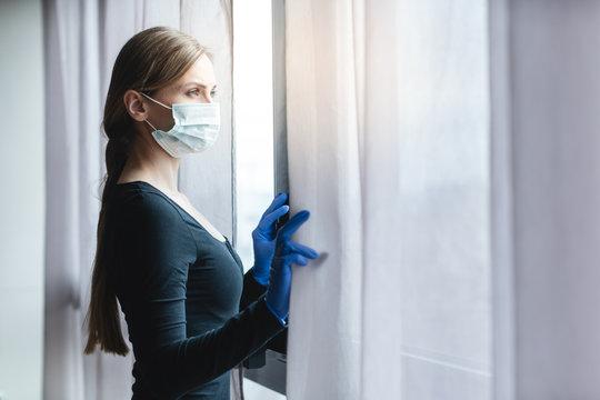 Bored woman in corona quarantine looking out of window