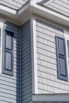 Two styles in one, gray shake and shingle siding and blue horizontal vinyl siding with matching blue shutters on a new single family home in America