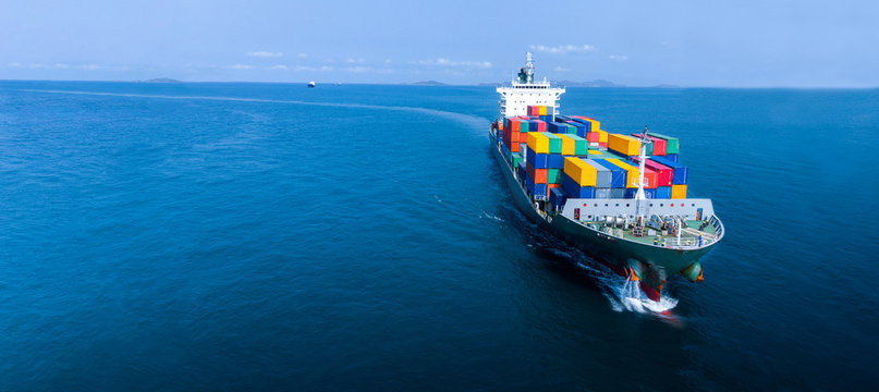 Aerial in front of cargo ship carrying container and running for export  goods  from  cargo yard port to custom ocean concept smart freight shipping by ship .