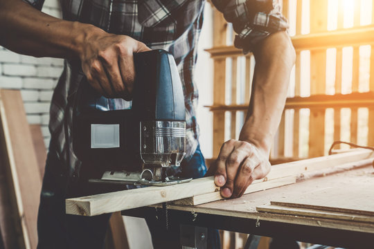 Carpenter working on wood craft at workshop to produce construction material or wooden furniture. The young Asian carpenter use professional tools for crafting. DIY maker and carpentry work concept.