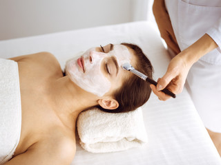 Photo sur Aluminium Spa Beautiful brunette woman enjoying applying cosmetic mask with closed eyes. Relaxing treatment in medicine and spa center concepts