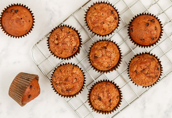Homemade banana muffins with chocolate chips and salted caramel on a marble background. Delicious and healthy dessert for Breakfast. Selective focus, top view