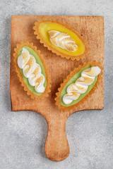 Shortbread cake baskets dough with fruit puree (Apple, mango, peach, melon)  and meringue. Delicious crunchy dessert for gourmets. Selective focus, top view
