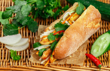 Baguette sandwich with fried chicken and fresh vegetables-carrots, cucumber, daikon, red pepper and cilantro (coriander) on a wicker table. Delicious fast food. Vietnamese Banh Mi. Selective focus