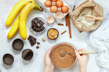 Woman prepares dough for homemade muffins with banana and chocolate. Whisk for whipping in hands. Ingredients on the table - wheat flour, eggs, brown sugar, chocolate chips, fresh fruit, cinnamon