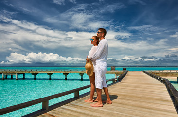 Wall Mural - Couple on a beach jetty at Maldives