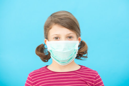 Little girl in a protective medical face mask on a blue background. Coronavirus Protection Concept, COVID-19.