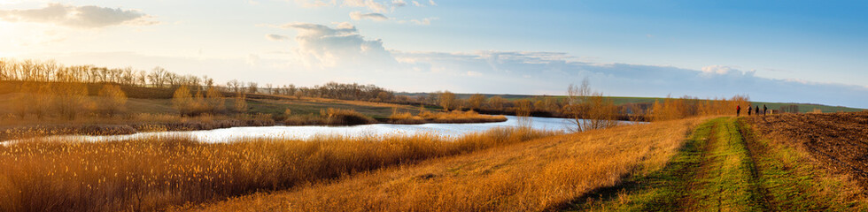 Panorama of steppe lake among fields and meadows during early spring. Countryside landscape.