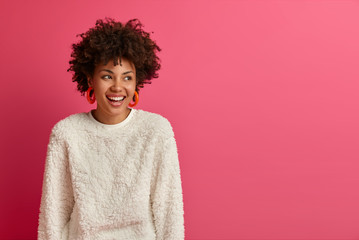 Portrait of dreamy good looking woman with Afro hairstyle, looks away and laughs, discusses funny...