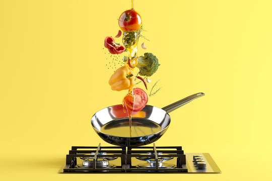 Fresh colored vegetables and olive oil flying from the stainless steel frying pan. At the bottom - a cooking stove with burning fire. Yellow studio background
