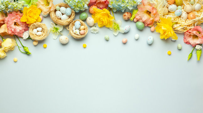 Happy Easter concept with easter eggs in nest and spring flowers. Easter background with copy space. Flat lay.
