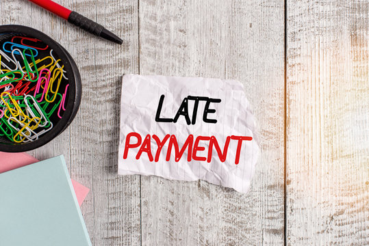 Text sign showing Late Payment. Business photo text payment made to the lender after the due date has passed Wrinkle paper and notebook plus stationary placed above wooden background