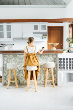 Young woman sitting alone behind a bar stand in a bright kitchen. From behind