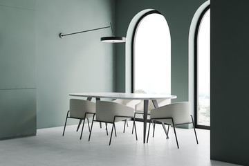 Green dining room corner with arched windows