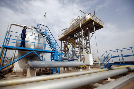 A worker sprays disinfectant as a preventive measure against coronavirus, at Nahr Bin Umar oil field, north of Basra