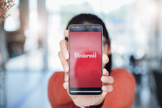 Chiangmai, Thailand - Mar 08, 2020 : Oneplus 6 showing Pinterest application on mobile. It was held by man hand in cafe shop.
